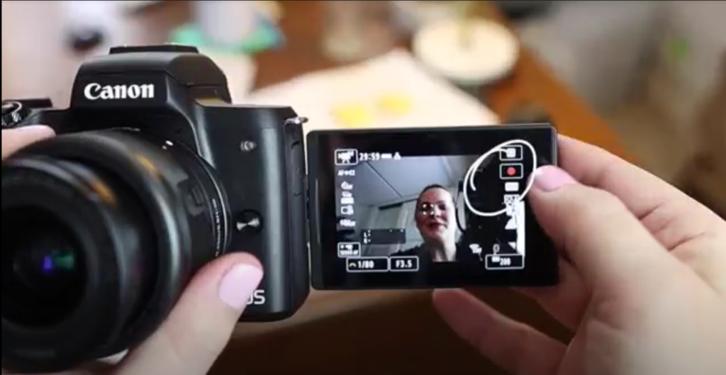 Meredith is showing the record button on the Canon m50 Mark ii.